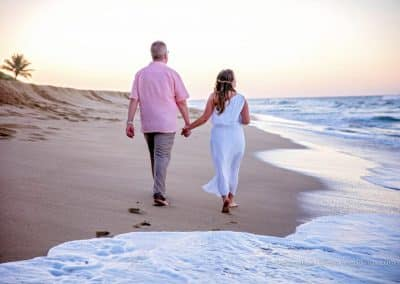 bride and groom walk on beach