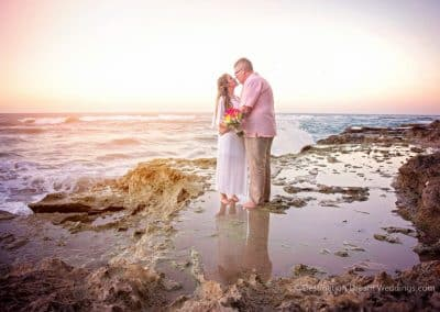 bride kissing groom on beach
