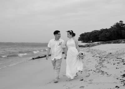 bride and groom walk down beach
