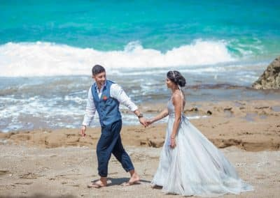 bride and groom walk on beach mexico