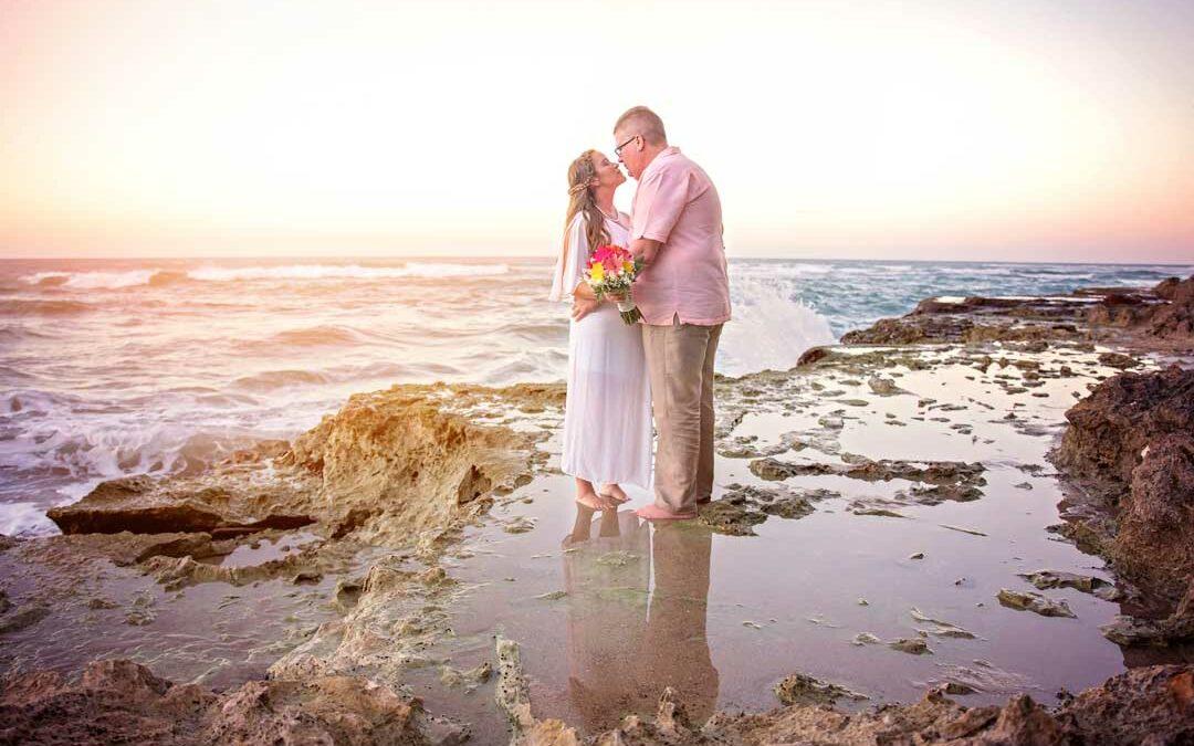husband kiss wife on beach